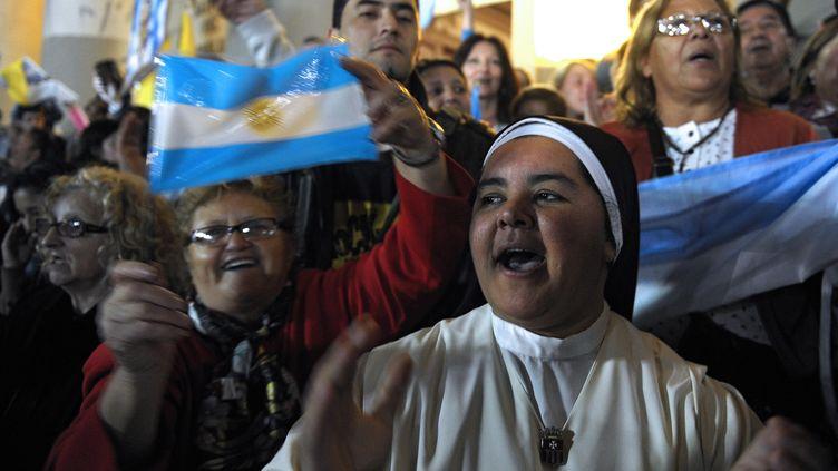 Des fidèles célèbrent l'élection du pape François, le 13 mars 2013 à Buenos Aires (Argentine). (ALEJANDRO PAGNI / AFP)
