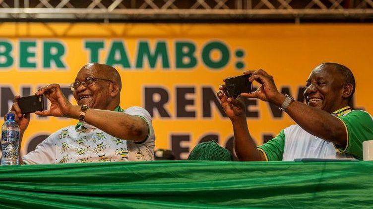 Jacob Zuma (à gauche) et Cyril Ramaphosa photographient avec leur smartphone les participants du congrès de l'ANC en décembre 2017 en Afrique du Sud. (MUJAHID SAFODIEN / AFP)