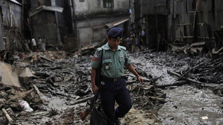 Un policier dans les ruines de l'incendie qui a détruit une partie du site historique de Dacca, le 03 juin 2010 (AFP/MUNIR UZ ZAMAN)