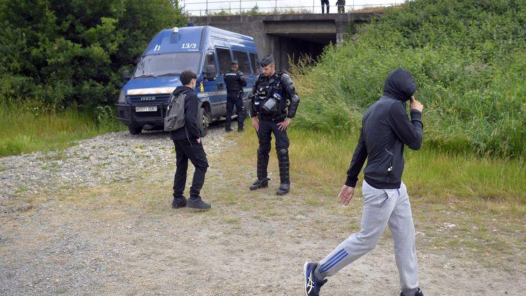 Des gendarmes devant des participants à une fête interditeà Redon (Ille-et-Vilaine),le 19 juin 2021. (LOIC VENANCE / AFP)