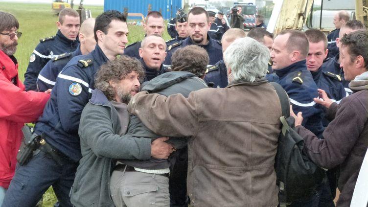 """Des gendarmes tentent d'empêcher des agriculteurs membres de la Confédération paysanne d'entrer sur le chantier de la ferme géante dite des """"mille vaches"""" à Drucat, près d'Abbeville (Somme), le 28 mai 2014. ( MAXPPP)"""
