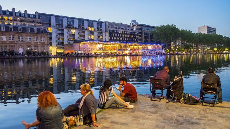 Des Parisiens au bord du bassin de la Villette, dans le 19e arrondissement, le 7 mai 2018. (GARDEL BERTRAND / AFP)