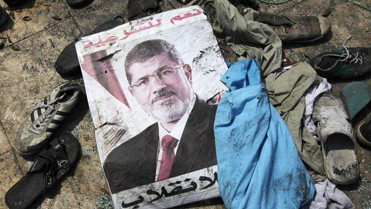 """Une affiche de Mohamed Morsi, sur laquelle est écrit """"Oui à la légitimité, non au coup d'Etat"""", le 15 août 2013, au milieu des débris d'un camp de manifestants évacué la veille, au Caire (Egypte). (MOHAMED ABD EL GHANY / REUTERS)"""