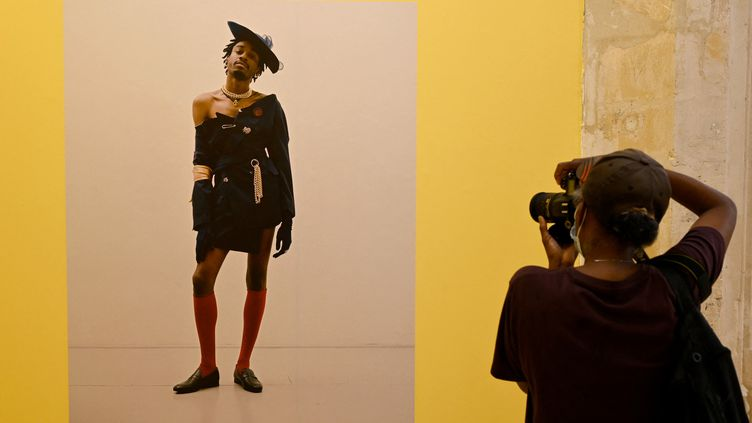 Unevisiteuseprend une photo à l'exposition New Black Vanguardà l'ouverture des Rencontres d'Arles, le 4 juillet 2021 (NICOLAS TUCAT / AFP)