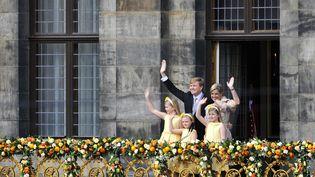 Le roiWillem-Alexander des Pays-Bas, son épouse, la reine Maxima and leurs filles;Catharina-Amalia, princesse d'Orange (à gauche), la princess Ariane (à droite) et la princesse Alexia (au centre), saluent la foule le30 avril 2013, jour du courronnement du roi. (REMKO DE WAAL / ANP / AFP)