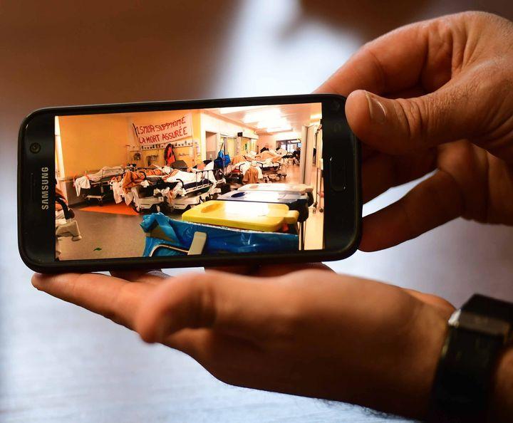 Un membre du personnel de l'hôpital de Lons-le-Saunier (Jura) montre une photo de l'engorgement des urgences, lors d'un mouvement de grève le 21 janvier 2019. (MAXPPP)