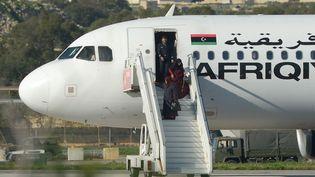 Des passagers de l'avionlibyen détourné à La Valette (Malte) sont libérés, le 23 décembre 2016 (MATTHEW MIRABELLI / AFP)