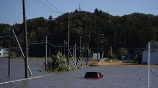 Une voiture coincée sur une route inondée à la suite du typhon Hagibis à Kakuda, préfecture de Miyagi, le 13 octobre 2019. (CHARLY TRIBALLEAU / AFP)