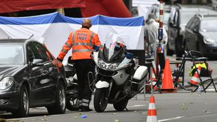 Un policier sécurise l'emplacement de la fusillade qui a fait trois morts mardi matin à Liège. (ERIC LALMAND / BELGA)