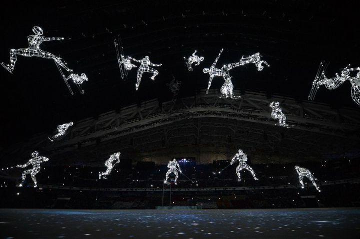 Des figures représentant différentes disciplines sportives scintillent dans le stade de Sotchi (Russie) pour l'ouverture des JO, le 7 février 2014. (ALBERTO PIZZOLI / AFP)