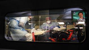 Du personnel médical installe un patient atteint du Covid-19 dans un TGV médicalisé, en gare de Paris-Austerlitz, le 1er avril 2020. (THOMAS SAMSON / AFP)