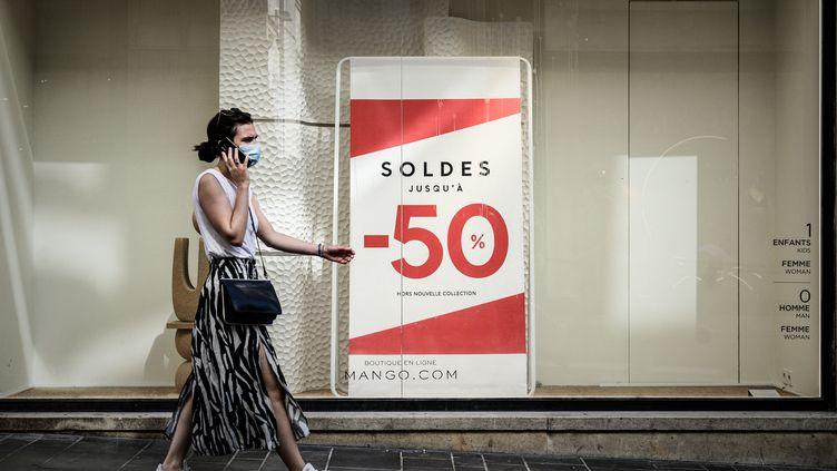 Une femme passe devant un magasin avec une enseigne de soldes à Bordeaux, le 18 juillet 2020. (PHILIPPE LOPEZ / AFP)