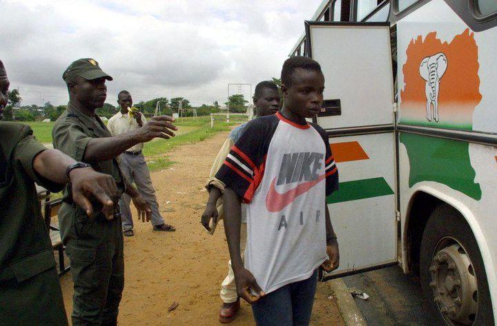 Des enfants burkinabè destinés aux plantations de cacao débarquent d'un bus à Abidjan après avoir été interceptés par la police le 1er juin 2001. (Photo AFP/Issouf Sanogo)