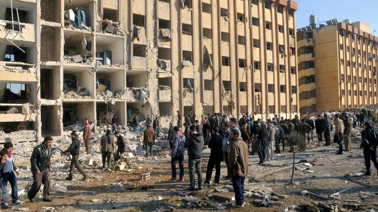 Une photo diffusée par l'agence de presse officielle syrienne montre des personnes massées devant l'université d'Alep (Syrie), touchée par une double explosion, le 15 janvier 2013. ( SANA / AFP)