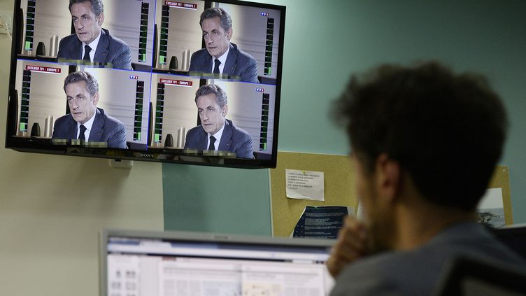 Un journaliste regarde à la télévision l'interview de NicolasSarkozy sur TF1, mercredi 2 juillet 2014. (STEPHANE DE SAKUTIN / AFP)