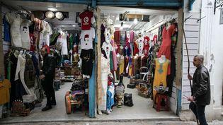 Un commerçant tire le rideau de sa boutique dans la médina de Tunis, qui s'est vidée de ses touristes en raison du coronavirus. Photo prise le 18 mars 2020. (AFP - CHEDLY BEN IBRAHIM / HANS LUCAS)