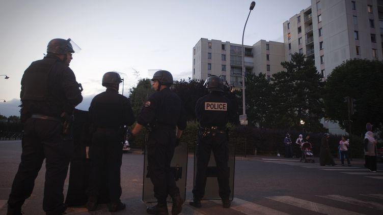 Des policiers stationnent dans la cité des Tarterêts (Corbeil-Essonnes), le 6 juin 2011, au lendemain des échauffourrées durant lesquelles une fillette a été blessée. (JOEL SAGET / AFP)