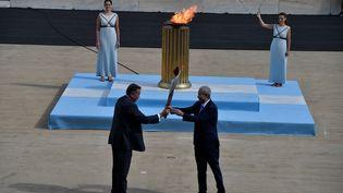 Le Président du comité olympique hellénique Spyros Kapralos a donné une lanterne contenant la flamme au vice-président du comité d'organisation Pékin-2022 Yu Zaiqing, le mardi 19 octobre 2021. (LOUISA GOULIAMAKI / AFP)