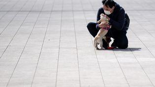 Un homme porte un masque contre le coronavirus Covid-19 et enlasse son chien, à Tokyo le 12 mars 2020. (PHILIP FONG / AFP)