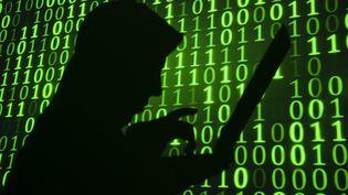 Une silhouette tape sur son ordinateur portable devant un mur de 0 et de 1. (BILL HINTON / MOMENT MOBILE ED)