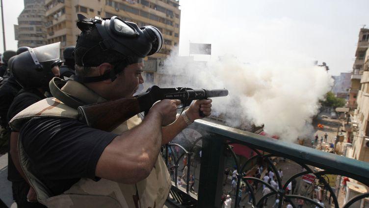 Un policier tire une bombe lacrymogène en direction de partisans des Frères musulmans, le 14 août 2013, au Caire (Egypte). (MOHAMED ABD EL GHANY / REUTERS)