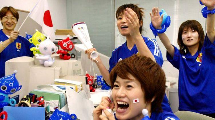 Des employés de l'entreprise de jouets Takara, à Tokyo, fêtent la victoire de leur équipe nationale de football.  (AFP PHOTO/Yoshikazu TSUNO)
