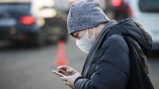 Un homme se protège de la pollution avec un masque, le 23 janvier 2017, à Paris. (GEOFFROY VAN DER HASSELT / AFP)