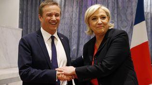Nicolas Dupont-Aignan et Marine Le Pen se serrent la main à l'issue d'une conférence de presse commune, le 29 avril 2017, à Paris. (GEOFFROY VAN DER HASSELT / AFP)