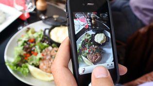 Une personne prend en photo son assiette avec son smartphone, le 19 juillet 2012, dans un restaurant de Paris. (ANA AREVALO / AFP)