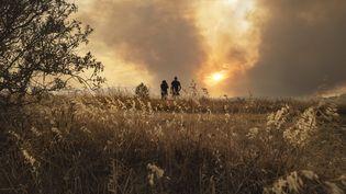 Des personnes observent le feu qui ravage une forêt, à Fabrezan (Aude), le 24 juillet 2021. (IDRISS BIGOU-GILLES / AFP)
