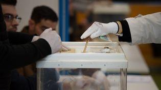 Une personne dépose son bulletin dans l'urne lors du premier tour des municipales, le 15 mars 2020, à Marseille. (CHAMUSSY/SIPA)