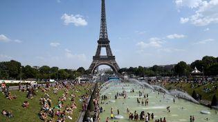 Des personnes dans la fontaine du Trocadéro, près de la tour Eiffel à Paris, le 25 juillet 2019. (BERTRAND GUAY / AFP)