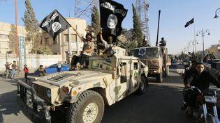 Des jihadistes de l'Etat islamique paradent dans la ville de Raqqa, peu après la prise de la ville, le 30 juin 2014. (STRINGER / REUTERS)