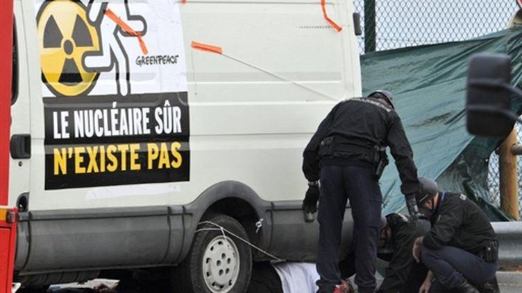 Des gendarmes s'apprêtent à évacuer un militant de Greenpeace, à Flamanville, le 2 mai 2011. (AFP - Jean-Paul Barbier)