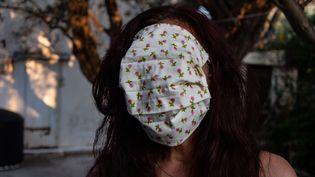Une adulte porte un masque distribué dans les écoles en Grèce, le 15 septembre 2020, dans la ville de Nea Artaki. (WASSILIS ASWESTOPOULOS / HANS LUCAS / AFP)