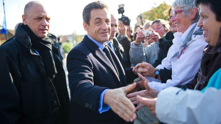 Nicolas Sarkozy salue des badauds avant une table ronde avec des agriculteurs, mardi 29 novembre à Gimont (Gers). (FREDERIC LANCELOT / SIPA)