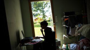 Une femme en télétravail chez elle. Photo d'illustration. (LOIC VENANCE / AFP)