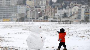 Un enfant s'approche d'un bonhomme de neige sur la plage du Havre (Seine-Maritime), le 13 janvier 2010. (MAXPPP)