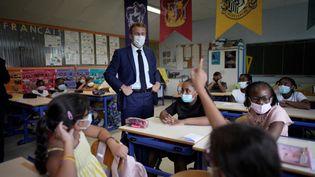 Emmanuel Macron pose avec des élèves masqués dans une école primaire à Marseille, le 2 septembre 2021. (DANIEL COLE / POOL / AFP)