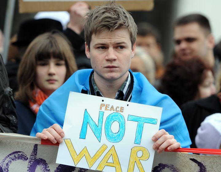 Un manifestant tient une pancarte pacifiste, lors d'une manifestation devant l'ambassade russe à Berlin (Allemagne), le 2 mars 2014. (BRITTA PEDERSEN / DPA)