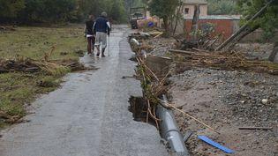 Deux personnes marchent sur une route détruite après les intempéries, le 16 octobre 2018, à Villalier (Aude). (PASCAL PAVANI / AFP)