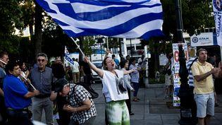 """Une femme fête la victoire du """"non"""" au référendum grec, place Syntagma, à Athènes, dimanche 5 juillet 2015. (ANGELOS TZORTZINIS / AFP)"""