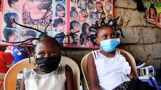 """Deux petites filles kenyanes avec la coiffure traditionnelle Bantu Knots, rebaptisée """"corona"""" par le coiffeur d'un salon du bidonville de Kibera à Nairobi, le 29 avril 2020.  (THOMAS MUKOYA / X90150)"""