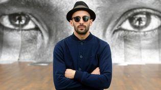 Le photographe français JR le 27 février 2014 devant une de ses oeuvres exposée au musée Frieder Burda à Baden-Baden  (ULI DECK / DPA / DPA PICTURE-ALLIANCE/AFP)