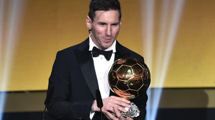 Lionel Messi pose avec son cinquième Ballon d'Or (FABRICE COFFRINI / AFP)