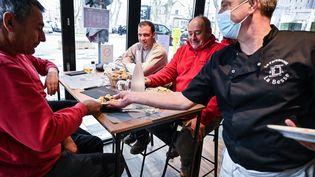 Un restaurateur sert le déjeuner à des travailleurs du bâtiment,comme la loi lui permet, dans son établissement de Tournon-sur-Rhône (Rhône), le 2 février 2021. (PHILIPPE DESMAZES / AFP)