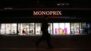 Un homme passe devant un supermarché Monoprix le soir, le 2 octobre 2013 à Paris. (THOMAS SAMSON / AFP)