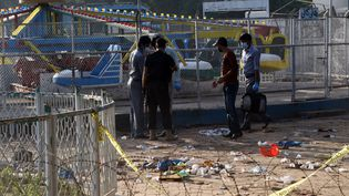 Des policiers relevant des indices sur le lieu d'un attentat commis dimanche 27 mars dans un parc bondé de Lahore (Pakistan), à proximité de jeux pour enfants. (ARIF ALI / AFP)