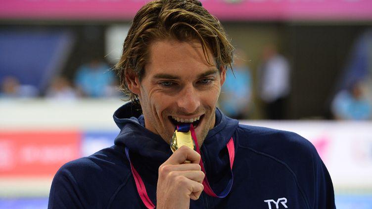 Camille Lacourt croque sa médaille d'or du 50 m dos aux championnats d'Europe de natation de Londres, le 19 mai 2016. (GLYN KIRK / AFP)