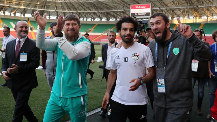 L'attaquant égyptien Mohamed Salah (en blanc) est accompagné par le leader tchétchène Ramzan Kadyrov (en survêtement vert et blanc), le 10 juin 2018, en marge d'un entraînement de l'Egypte à Grozny (Russie). (KARIM JAAFAR / AFP)